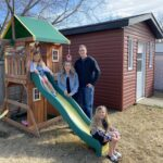 A family of four, mother, father and daughters in a backyard slide