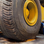 A worker standing beside a giant tire.